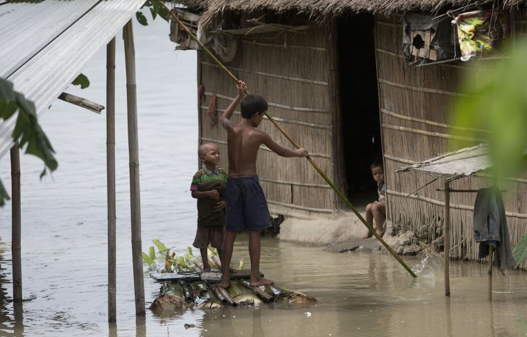 Indian children paddle a makeshift banana raft through a flood affected area in Burhaburh village, about 60 kilometers (37 miles) east of Gauhati, India , Saturday, Aug. 22, 2015. State authorities say that monsoon flooding has nearly 200,000 people to leave their homes and take shelter in state-run tents this week. The area is prone to flooding during the June-to-September monsoon season. (AP Photo/Anupam Nath)
