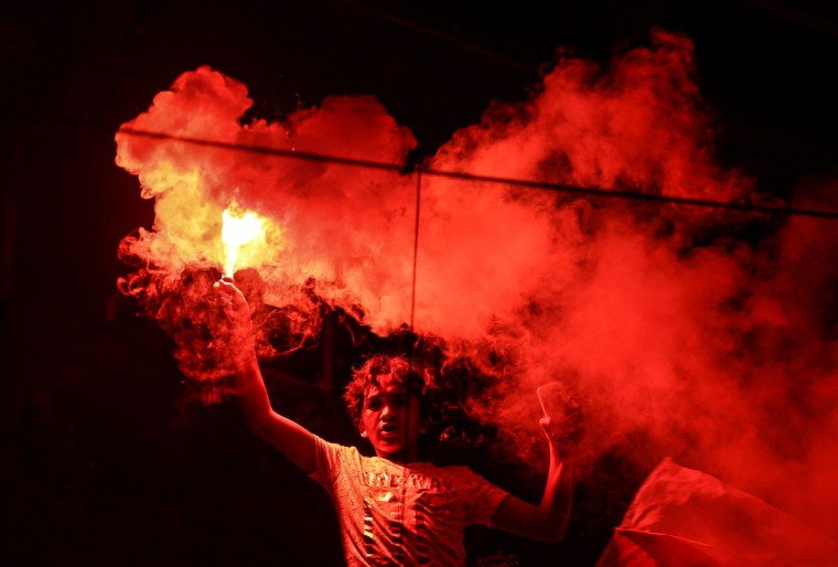 A member of Zamalek's football club's Ultras White Knights group (UWK), the club's hardcore fan base, lights flares during a friend's bachelor party in Cairo, Egypt. Ultras, whose name comes from the Latin word for ìbeyond,î started in Latin America and Europe in the 1950s and eventually made it to Arab countries, with particularly strong followings in North Africa. The first to form in Egypt, UWK, emerged in 2007 to support the Zamalek team. Groups backing arch-rival al-Ahly and others soon followed. (AP Photo/Mohammed El Raai)
