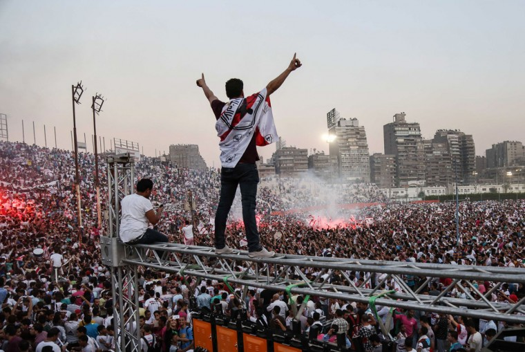 Zamalek soccer fans celebrate after winning the Egyptian League at Zamalek Club in Cairo, Egypt. The hardcore fan base Ultras White Knights did not celebrate the winning of the team out of respect for more than 20 soccer fans who were crushed to death outside an air defense stadium in Cairo after police fired tear gas to break up the crowd waiting in a fenced, narrow corridor to watch. Police accused the fans of attacking the force, and rioting to enter the stadium on Feb. 8, 2015. (AP Photo/Mohammed El Raai)