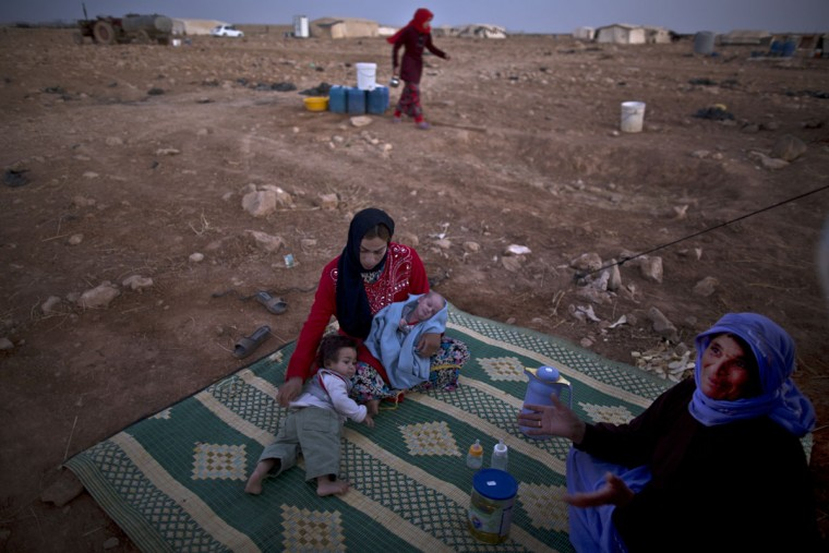 In this Thursday, July 23, 2015 photo, Syrian refugee Ruqayya Ahmad, 19, holds her 8-day old daughter Hikmiyya and her son Ali, 1,while sitting next to her mother in law Mayoufah, outside their tent to avoid the heat trapped inside, at an informal tented settlement near the Syrian border on the outskirts of Mafraq, Jordan. Ahmad, says she canít afford to take Hikmiyya to the doctor to have a rash she suffers from treated. (AP Photo/Muhammed Muheisen)