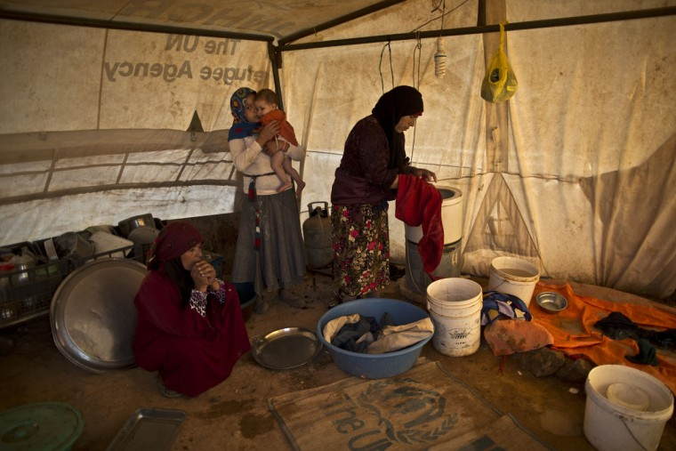 In this Wednesday, July 22, 2015 photo, a Syrian refugee girl holds her younger sister while her mother, right, washes clothes inside their tent at an informal settlement near the Syrian border on the outskirts of Mafraq, Jordan. Aid agencies asked for $4.5 billion for 2015 to help refugees, but have been forced to slash support programs because of large funding gaps. Thatís had a devastating effect on the amount of food aid coming. (AP Photo/Muhammed Muheisen)