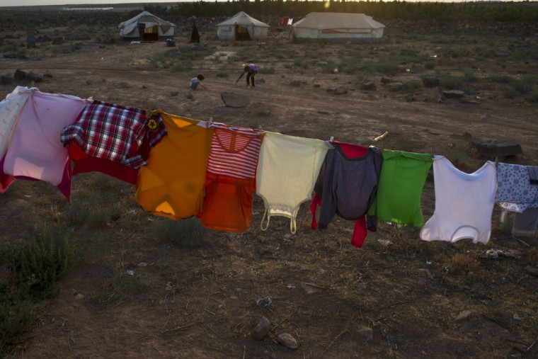 In this Monday, July 27, 2015 photo, clothes of Syrian refugee children hang out to dry outside a tent at an informal settlement near the Syrian border on the outskirts of Mafraq, Jordan. More than 10,000 children have died in Syria's four-year conflict, while over 2.8 million in and out of the country donít go to school, according to the U.N. children's agency, UNICEF. (AP Photo/Muhammed Muheisen)