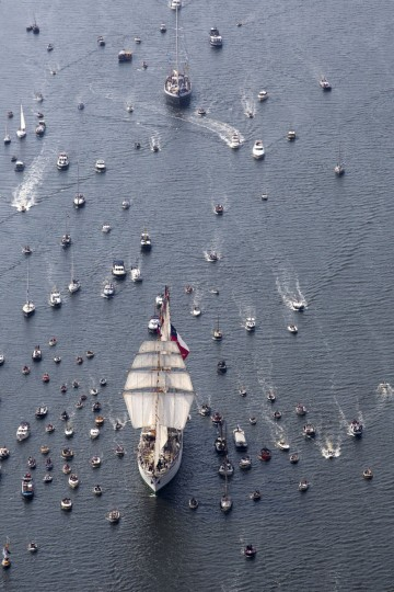 Tall ships escorted by small boats arrive in Amsterdam, Netherlands, Wednesday, Aug. 19, 2015, to participate in SAIL Amsterdam 2015, a five-yearly festival celebrating the Dutch capital's maritime history that is expected to draw some 2 million visitors. The 9th edition of the nautical event lasts until Sunday, Aug. 23 on and around the IJ river. (AP Photo/Cris Toala Olivares)