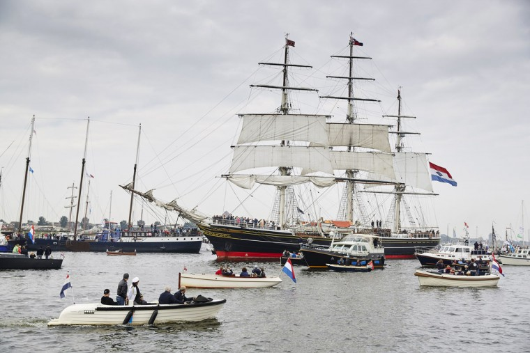 Small boats escort the historic clipper Stad Amsterdam (City of Amsterdam) as it sails to Amsterdam, Netherlands, Wednesday, Aug. 19, 2015, to participate in SAIL Amsterdam 2015, a five-yearly festival celebrating the Dutch capital's maritime history that is expected to draw some 2 million visitors. The 9th edition of the nautical event lasts until Sunday, Aug. 23 on and around the IJ river. (AP Photo/Phil Nijhuis)