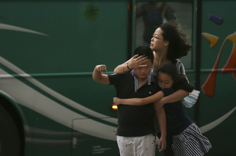 A mother holds her children in strong gusts from Typhoon Soudelor in Taipei, Taiwan, Friday, Aug. 7, 2015. Soudelor is expected to bring heavy rains and strong winds to the island late Friday with winds speeds over 170 km per hour (100 mph) and gusts over 200 km per hour (120 mph) according to Taiwan's Central Weather Bureau. (AP Photo/Wally Santana)