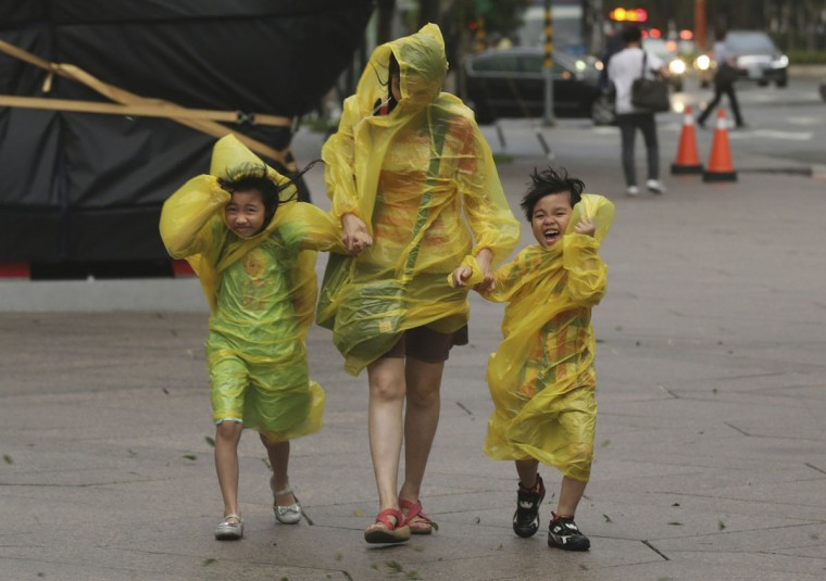 A woman and children brave the strong winds from Typhoon Soudelor in Taipei, Taiwan, Friday, Aug. 7, 2015. Soudelor is expected to bring heavy rains and strong winds to the island late Friday with winds speeds over 170 km per hour (100 mph) and gusts over 200 km per hour (120 mph) according to Taiwan's Central Weather Bureau. (AP Photo/Wally Santana)