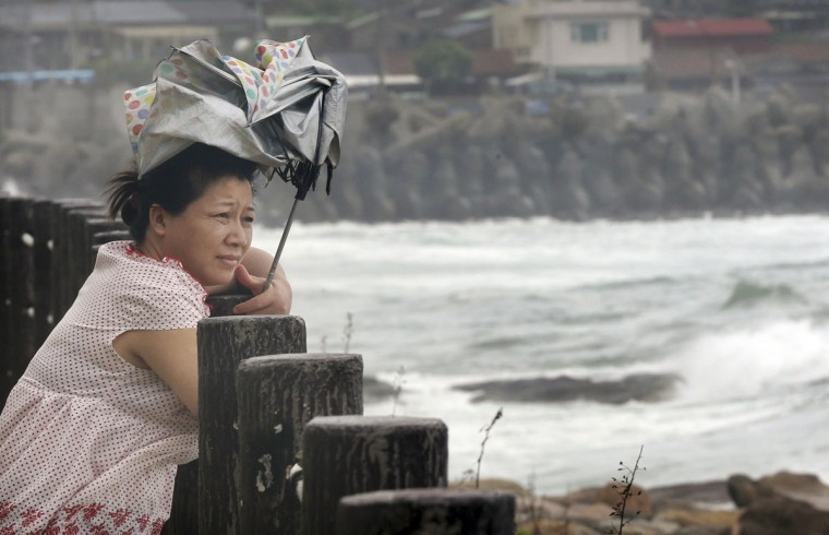 A woman braves the winds as she watches waves from approaching Typhoon Soudelor in Keelung, northeastern Taiwan, Friday, Aug. 7, 2015. Soudelor is expected to bring heavy rains and strong winds to the island late Friday with winds speeds over 170 km per hour (100 mph) and gusts over 200 km per hour (120 mph) according to Taiwan's Central Weather Bureau. (AP Photo/Wally Santana)