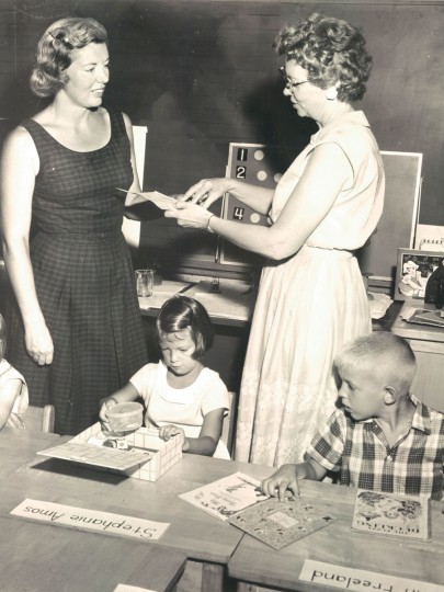 Mrs. Louise M. Barlow first grade teacher at Loch Raven Elementary School. Six year old Steffie subject of the conversation unpacks school kit as John Freeland looks on. (Edward Nolan/Baltimore Sun, 1961)