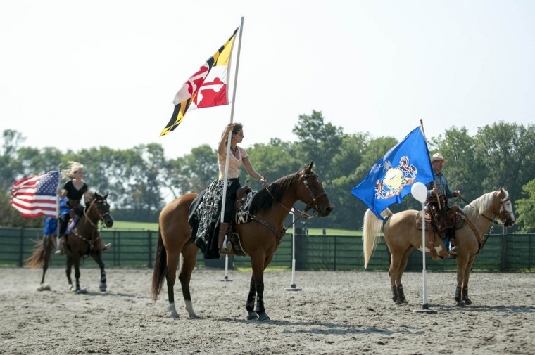 Jessica Flores, center, holds the Maryland State Flag during a flag ceremony before the start of a competition at Willowbrook Farms. (Tom Brenner, Baltimore Sun)