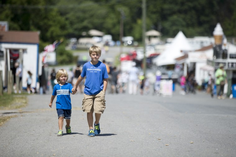 Rocco Gamber, left, 2, holds hands with his cousin Teagan Roosa, right, 9, both of Frederick during the 70th Annual Howard County Fair at the Howard County Fairgrounds in West Friendship, MD on Wednesday, August 12, 2015. (Jen Rynda/BSMG)