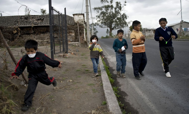 Children walk along a street covered with ashes of the Cotopaxi volcano in Lasso, Ecuador on August 23, 2015. A dozen towns of central Ecuador, including Quito sector, suffered Saturday the ashes of the Cotopaxi volcano, which started erupting a week ago after 138 years, as crops and cattle were affected. (MARTIN BERNETTI/AFP/Getty Images)