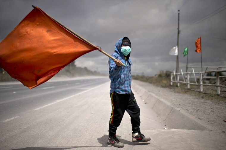 A boy wearing a face mask and holding a flag walks along a street covered with ashes of the Cotopaxi volcano in Lasso, Ecuador on August 23, 2015. A dozen towns of central Ecuador, including Quito sector, suffered Saturday the ashes of the Cotopaxi volcano, which started erupting a week ago after 138 years, as crops and cattle were affected. (MARTIN BERNETTI/AFP/Getty Images)