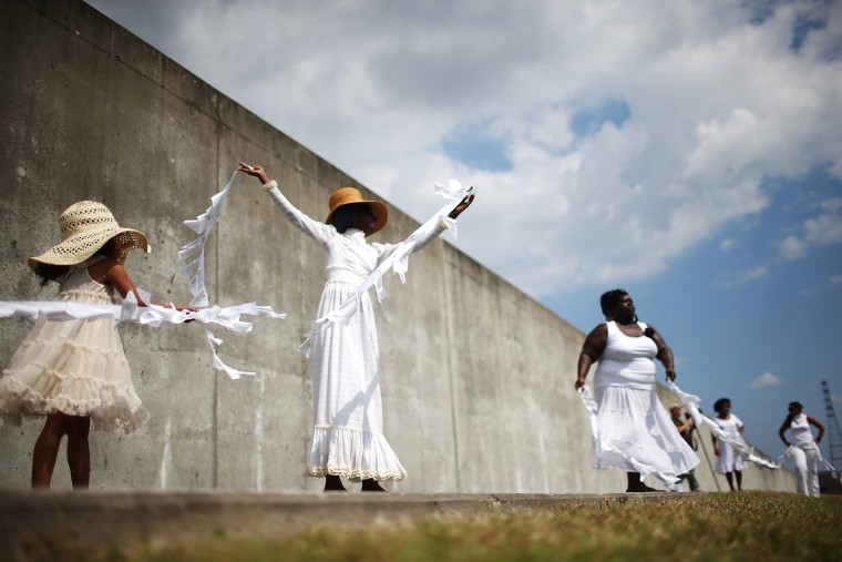 Performers from 'Gallery of the Streets' dance along the repaired levee wall in the Lower Ninth Ward during a ceremony marking the 10th anniversary of Hurricane Katrina on August 29, 2015 in New Orleans, Louisiana. A levee breach along the Industrial Canal in the Lower Ninth Ward devastated the area with massive flooding in the aftermath of Hurricane Katrina. (Mario Tama/Getty Images)