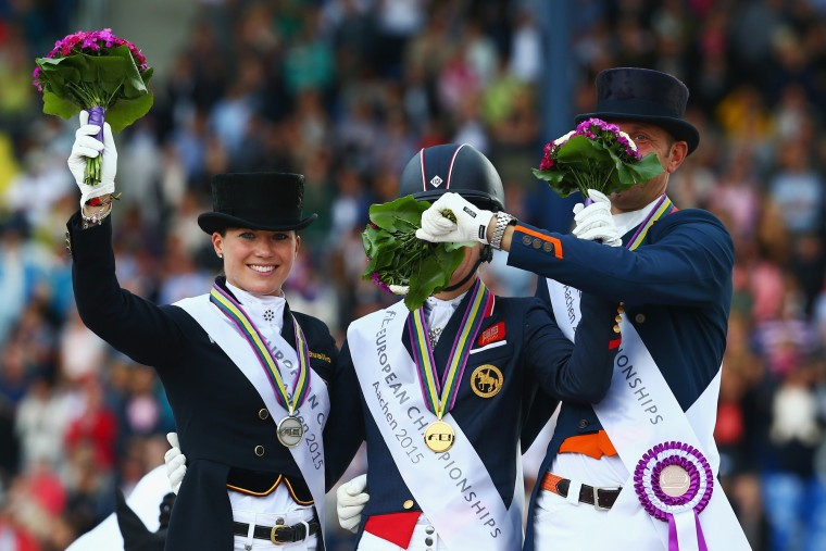 Charlotte Dujardin (C) of Great Britain celebrates winning the Dressage Grand Prix Special Individual Final with second placed Kristina Broering-Sprehe (L) of Germany and third placed Hans Peter Minderhout of the Netherlands on Day 4 of the FEI European Equestrian Championship 2015 on August 15, 2015 in Aachen, Germany. (Alex Grimm/Bongarts/Getty Images)