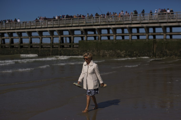 A woman walks at the beach as migrants demonstrate on top of a pier near the port, Calais, northern France, Saturday, Aug. 8, 2015. Some thousands of migrants have been scaling fences near the Channel Tunnel linking the two countries and boarding freight trains or trucks destined for Britain. (Emilio Morenatti/Associated Press)