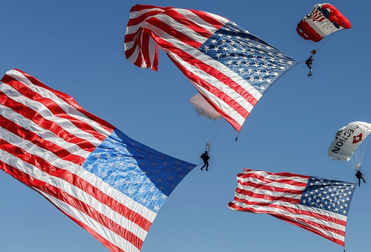 Parachuters fly over Lakota West's football field Saturday, Aug. 21, 2015, during the funeral service in West Chester, Ohio, for Army Master Sgt. Corey Hood. Hood, 32, a Lakota West graduate and member of the Army's Golden Knights parachute team, died Aug. 16 following a performance at the Chicago Air and Water Show. (Madison Schmidt/The Cincinnati Enquirer via AP)