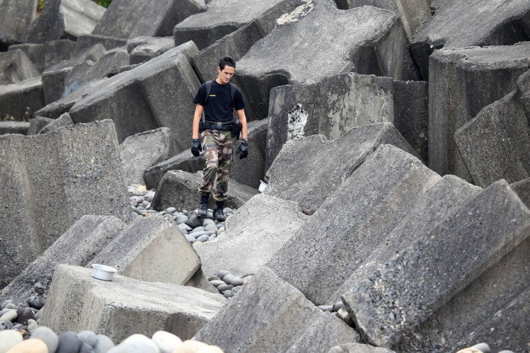 A police officer from Saint-Benoit's gendarmerie looks for debris from the ill-fated Malaysia Airlines flight MH370 on a beach in Sainte-Marie de la Reunion, on the French Reunion Island in the Indian Ocean, on August 8, 2015. France launched a hunt for more wreckage from the ill-fated MH370 plane off Reunion island on August 7 in a fresh effort to shed light on one of aviation's biggest mysteries. The tiny French Indian Ocean territory has been under intense scrutiny since a beach cleaner found a washed-up wing part last week, which Malaysian Prime Minister Najib Razak later declared was part of the Boeing 777 that mysteriously vanished 17 months ago. (Richard Bouhet/AFP-Getty Images)