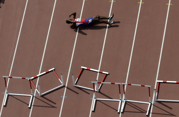Cuba's Yordani Garcia lays on the track after falling in a men's 110m hurdles decathlon heat at the World Athletic Championships at the Bird's Nest stadium in Beijing, Saturday, Aug. 29, 2015. (Wong Maye-E/Associated Press)