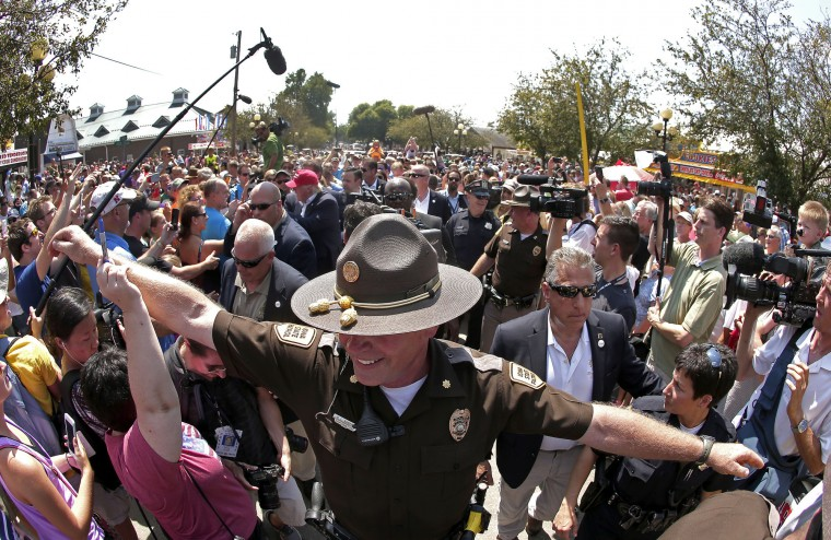 An Iowa State Trooper tries to clear a path through the crowd for Republican presidential candidate Donald Trump, center left in red hat, at the Iowa State Fair Saturday, Aug. 15, 2015, in Des Moines. (Charlie Riedel/Associated Press) ORG XMIT: IACR126