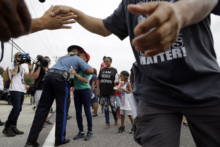 Missouri Highway Patrol Capt. Ron Johnson, left, gets a hug from a person participating in a parade in honor of Michael Brown Saturday, Aug. 8, 2015, in Ferguson, Mo. Sunday will mark one year since Michael Brown was shot and killed by Ferguson police officer Darren Wilson. (Jeff Roberson/Associated Press)