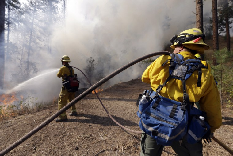 "Firefighters hose the edge of a controlled fire along a driveway being used as a fire break between houses and the main fire Saturday, Aug. 22, 2015, in Okanogan, Wash. Out-of-control blazes in north-central Washington have destroyed buildings, but the situation is so chaotic that authorities have ""no idea"" how many homes may have been lost. (Elaine Thompson/Associated Press)"