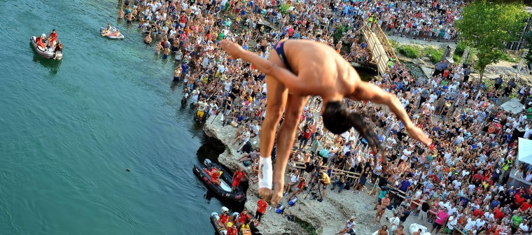 "People gather to attend the Cliff Diving World Series competition near the Stari Most bridge in Mostar on August 15, 2015. Competitors jump from a platform installed on Mostar's ""Old Bridge"", that crosses the Neretva river, where the height of the dive is around 28 meters, the dive takes about 3 seconds. (Elvis Barukcic/AFP-Getty Images)"
