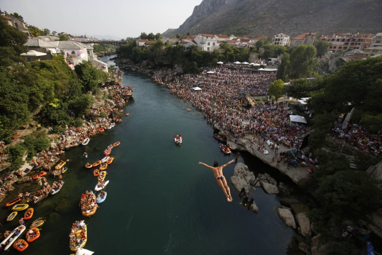 Spectators watch as a diver jumps from the Old Mostar Bridge during the sixth stop of the Red Bull Cliff Diving World Series 2015, in Mostar, 140 kms south of Bosnian capital of Sarajevo, Saturday, Aug. 15, 2015. Fourteen of the world's best competitors took part in the competition diving from a 27 meter high bridge over the river of Neretva. (Amel Emric/Associated Press)