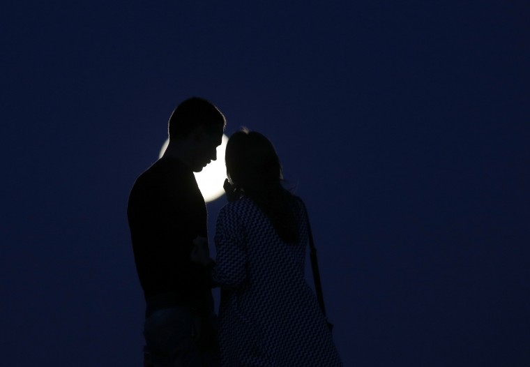 A young couple share a tender moment as a perigee moon, also known as a super moon, rises in the sky in the town of Novogrudok, 150 kilometers (93 miles) west of the capital Minsk, Belarus, Saturday, Aug. 29, 2015. The supermoon happens when moon is full and makes it closest approach to Earth in her orbit. (Sergei Grits/Associated Press)