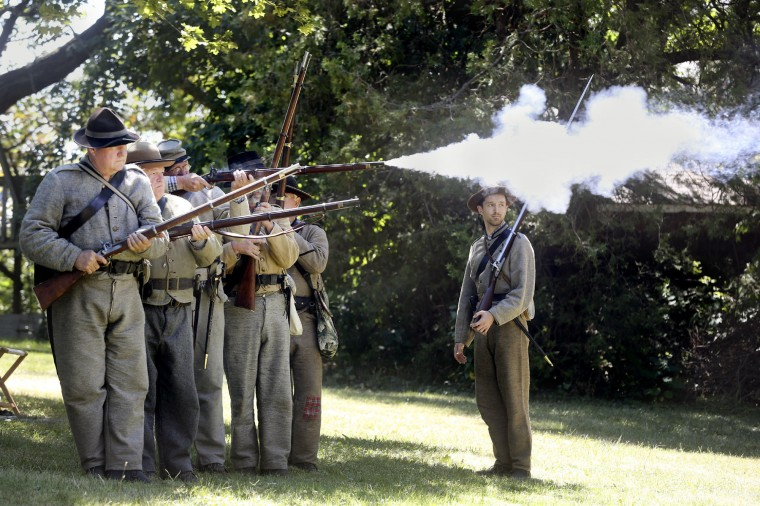 Members of the 4th Virginia Stonewall Brigade Civil War reenactment group take turns firing their muskets Saturday, Aug. 22, 2015, during the First Annual Family Fun and History Days at Stonewall Jackson's Headquarters Museum in Winchester, Va. (Scott Mason /The Winchester Star via AP)