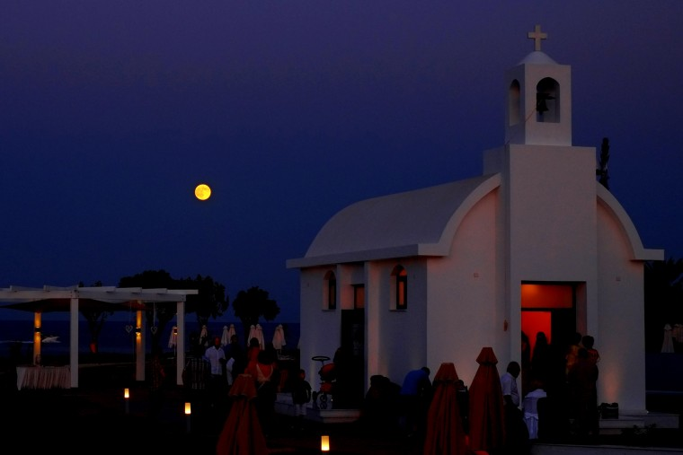 The full moon rises over a small Christian orthodox church during a wedding ceremony at Protaras resort in the southeast part of the island of Cyprus, Saturday, Aug. 29, 2015. (Petros Karadjias/Associated Press)