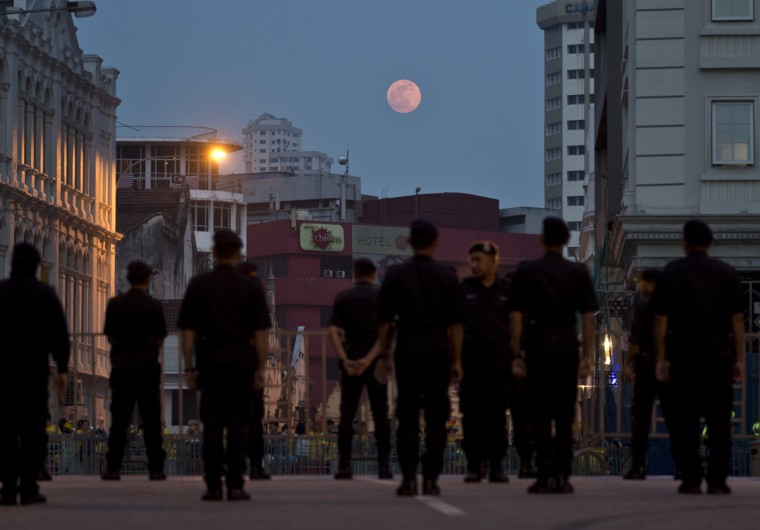 Malaysian Police personnel stand guard during an anti-government rally near Independence square in Kuala Lumpur as moon rises on August 29, 2015. Tens of thousands of Malaysians streamed into central Kuala Lumpur to call for the prime minister's ouster over corruption allegations and demand broader reforms, spurning warnings by police who have declared the rally illegal. (Manan Vatsyayana/AFP-Getty Images)