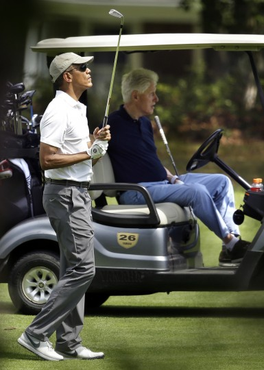 President Barack Obama, left, watches the flight of his ball as former President Bill Clinton, right, watches while golfing Saturday, Aug. 15, 2015, at Farm Neck Golf Club, in Oak Bluffs, Mass., on the island of Martha's Vineyard.(Steven Senne/Associated Press)