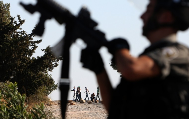 An Israeli border guard holds up his weapon during clashes with Palestinian stone throwers following the funeral Saad Dawabsha, the father of a Palestinian toddler killed last week when their home was firebombed by Jewish extremists, on August 8, 2015 in the West Bank village of Duma. Dawabsha died in hospital in the southern Israeli city of Beersheba where he was being treated for third-degree burns for the past eight days. (Jaafar Ashtiyeh/AFP-Getty Images)