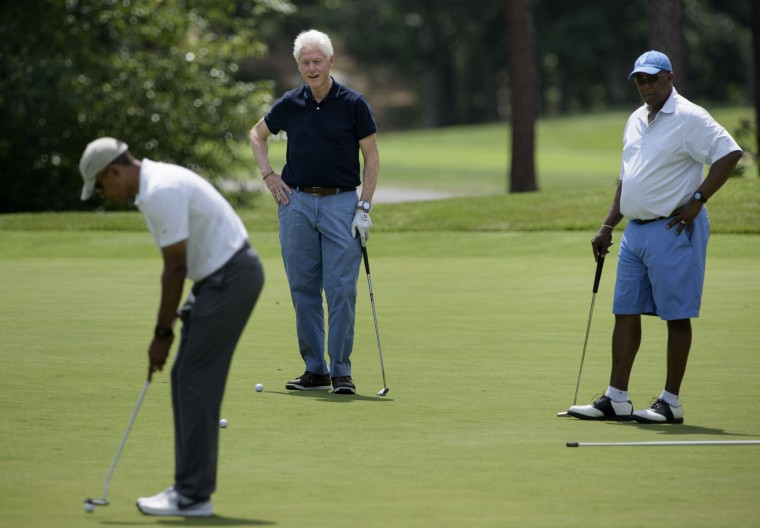 Former US President Bill Clinton (C) and Ron Kirk (R) watch as US President Barack Obama putts while golfing at Farm Neck Golf Club August 15, 201)Brendan Smialowski/AFP-Getty Images)