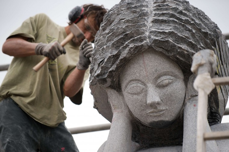 A sculptor works on the statue of a Breton Saint in Carnoet, western France, on the site of the Valley of Saints (Vallee des Saints). The Valley of Saints is a sort of contemporary Easter Island in Brittany with some 60 monumental sculptures of Breton Saints. 100,000 people visited this valley in 2014, which was inaugurated in 2012. (Jean-Sebastian Evrard/AFP-Getty Images)