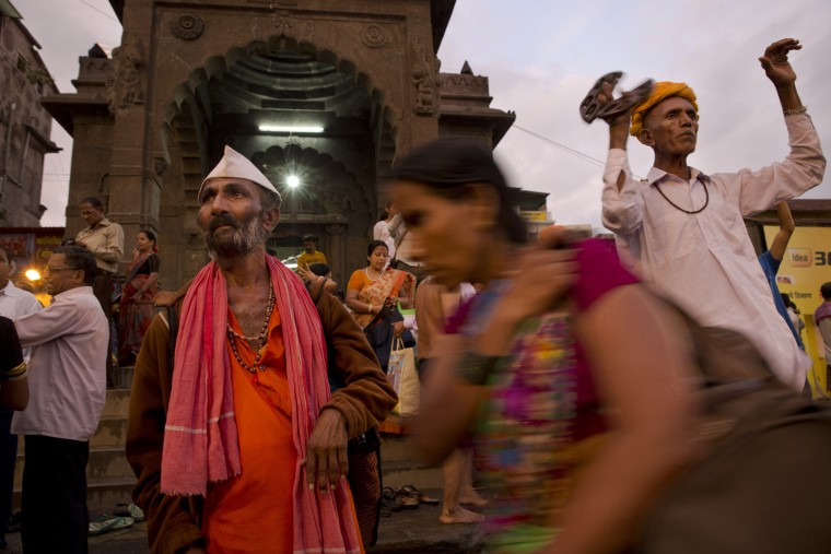 An Indian devotee, right, sings a religious song as others move after bathing in the Godavari river during Kumbh Mela, or Pitcher Festival, in Nashik, India, Saturday, Aug. 29, 2015. Hindus believe taking a dip in the waters of a holy river during the festival will cleanse them of their sins. (Tsering Topgyal/Associated Press)