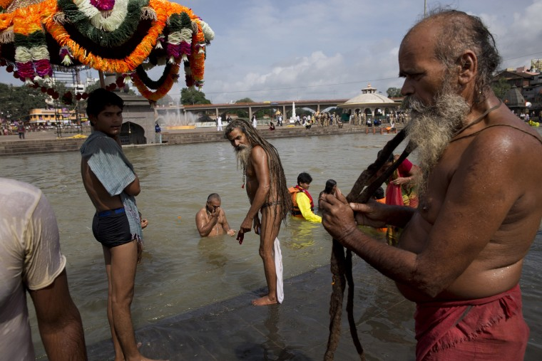 An Indian Sadhu, or Hindu holy man, right, dries his hair after a bath as others take a bath in the Godavari River during Kumbh Mela, or Pitcher Festival, in Nashik, India, Saturday, Aug. 29, 2015. Hindus believe taking a dip in the waters of a holy river during the festival will cleanse them of their sins. (Tsering Topgyal/Associated Press)