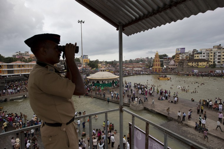 An Indian police looks though a binocular as devotees bath in the Godavari River during Kumbh Mela, or Pitcher Festival in Nashik, India, Saturday, Aug. 29, 2015. Hindus believe taking a dip in the waters of a holy river during the festival will cleanse them of their sins. (Tsering Topgyal/Associated Press)