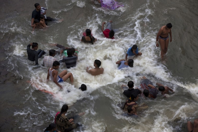 Indian devotees bath in the Godavari River during Kumbh Mela, or Pitcher Festival in Nashik, India, Saturday, Aug. 29, 2015. Hindus believe taking a dip in the waters of a holy river during the festival will cleanse them of their sins. (Tsering Topgyal/Associated Press)