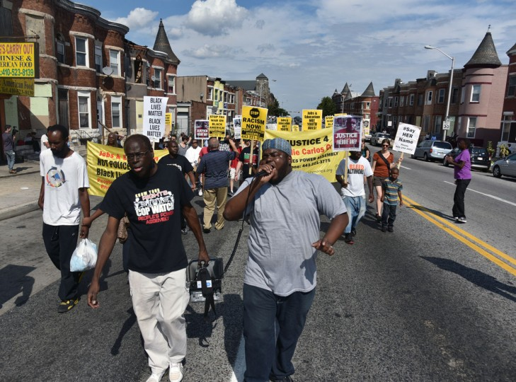 Left to right, Andre Powell, an organizer with Baltimore People's Power Assembly, and Rev. C. D. Witherspoon, president of the Baltimore SCLC, lead a march on North Avenue. The Baltimore People's Power Assembly holds a march on the one year anniversary of the death of Michael Brown. Brown, 18, was shot by a police officer in Ferguson, Mo. The march began at Pennsylvania and North Avenues and is moving through the neighborhood to the place where Freddie Gray was arrested before continuing to N. Charles Street. Gray died in the custody of Baltimore City police. (Kim Hairston/Baltimore Sun)