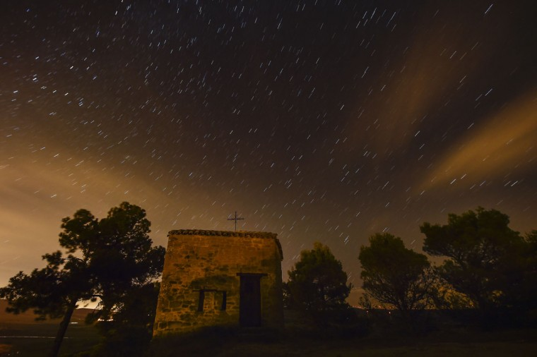 "Stars seen as streaks from a long camera exposure are seen behind Arnotegui Hermitage, in Obanos, northern Spain, Tuesday, Aug. 11, 2015. Some Catholics refer to the Perseids as the ""tears of Saint Lawrence"", since August 10 is the date of that saint's martyrdom. (AP Photo/Alvaro Barrientos)"