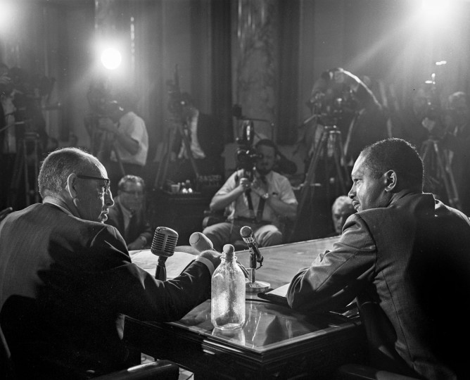 Los Angeles Police Chief William Parker, left, faces Councilman Thomas Bradley as he testifies in front of a City Council committee on the sequence of events leading up to the Watts Riots on Sept. 13, 1965. On the table is a Molotov cocktail that Parker said was found during riot. (John Malmin/Los Angeles Times/TNS)