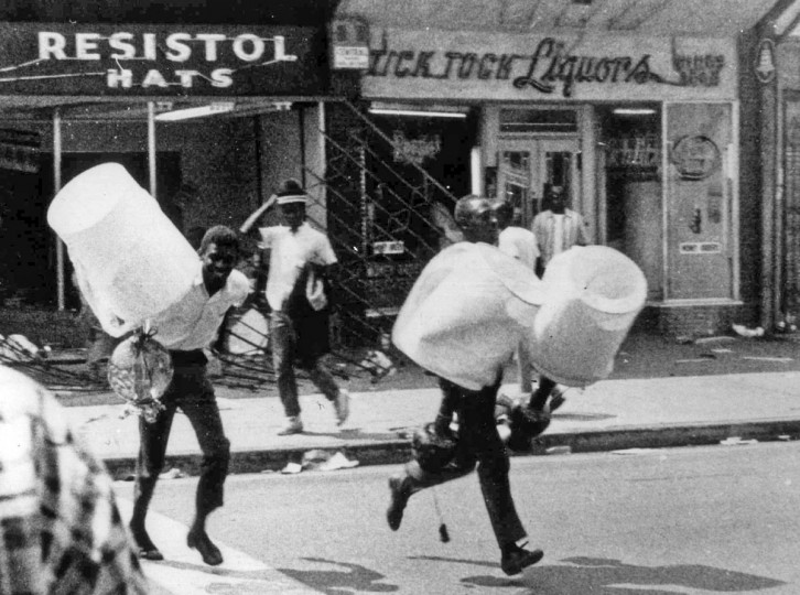 FILE - In this Aug. 13, 1965 file photo, men carry items from a looted store during the rioting that enveloped the Watts district of Los Angeles. It began with a routine traffic stop 50 years ago this month, blossomed into a protest with the help of a rumor and escalated into the deadliest and most destructive riot Los Angeles had seen. The Watts riot broke out Aug. 11, 1965 and raged for most of a week. When the smoke cleared, 34 people were dead, more than a 1,000 were injured and some 600 buildings were damaged. (AP Photo, File)