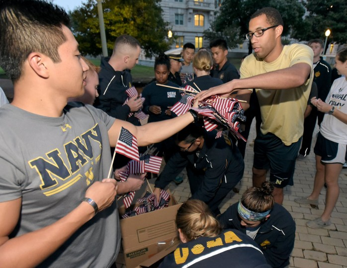 Midshipman 1st Class Peter Guo, left, hands out flags to Midshipman 3rd Class Brandon Alford. Midshipmen at the U.S. Naval Academy placed 2977 flags along Stribling Walk, one for each person killed in the September 11th Attacks on the World Trade Center and Pentagon. The event was sponsored by the Midshipmen Action Group.