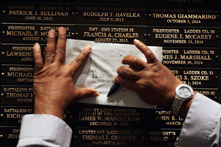 Family members copy the names of loved ones at a ceremony at the Fire Department of New York headquarters where names were added to a memorial wall for deaths related to World Trade Center illnesses on September 8, 2015 in New York City. A total of 21 names were added to the memorial which was unveiled in September 2011 and already lists the names of 89 FDNY members who died of illnesses related to their work at the World Trade Center site during and after the 9/11 attacks. (Photo by Spencer Platt/Getty Images)
