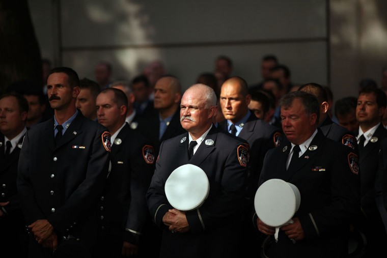 Firefighters attend a ceremony at the Fire Department of New York headquarters where names were added to a memorial wall for deaths related to World Trade Center illnesses on September 8, 2015 in New York City. A total of 21 names were added to the memorial which was unveiled in September 2011 and already lists the names of 89 FDNY members who died of illnesses related to their work at the World Trade Center site during and after the 9/11 attacks. (Photo by Spencer Platt/Getty Images)