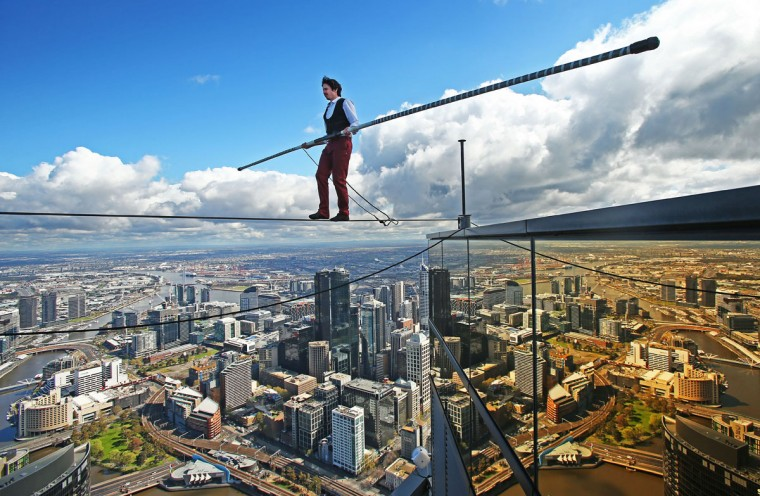 High-wire artist Kane Petersen successfully walks a tightrope 300 metres above the ground at Eureka Skydeck on September 16, 2015 in Melbourne, Australia. The walk was the highest tightrope walk ever attempted in the Southern Hemisphere. The stunt is to mark the arrival of the film 'The Walk' to Australian cinemas in October. The stunt saw Kane mimic the film's French high-wire artist Philippe Petit, who successfully walked between the twin towers of the World Trade Center in 1974. (Photo by Scott Barbour/Getty Images)