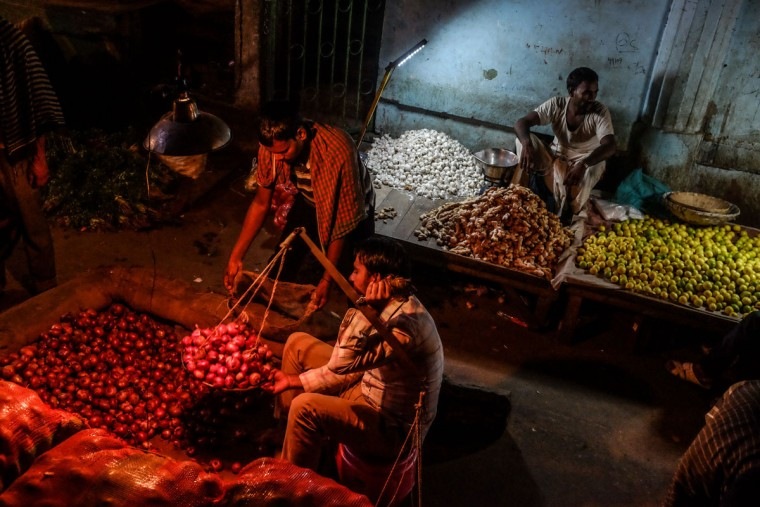An Indian seller weighs a measure of onions on a hand-held scale (L) at a local market in south New Delhi on September 9, 2015. The cost of India's staple vegetable -- an essential ingredient in curries and eaten daily by almost everyone -- soared in August to an eyewatering 60 rupees (90 US cents) a kilo on wholesale markets, up from 25 rupees in June. (AFP Photo/ Roberto Schmidt)