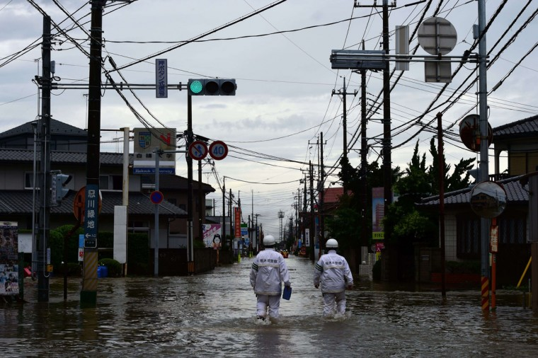 Police officers walk through floodwaters to search for evacuees in Oyama, Tochigi prefecture, north of Tokyo on September 10, 2015. Authorities in central Japan ordered tens of thousands to flee their homes after torrential rains flooded rivers and triggered landslides, with one person missing after a mudslide buried houses. The Japan Meteorological Agency issued special downpour warnings for Tochigi and Ibaraki prefectures, north of Tokyo, urging vigilance against mudslides and flooding. (AFP Photo/Yoshikazu Tsuno)