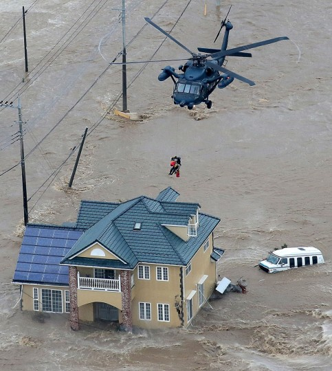 Local residents are rescued from their flooded home by a helicopter of the Ground Self Defence Force in Joso, Ibaraki Prefecture, on September 10, 2015. The Japanese city 50 km north east of Tokyo was flooded when Kinugawa river burst its banks, destroying homes and cars as desperate residents waited for help, and as thousands of people were ordered to evacuate. (AFP Photo/P /jiji )